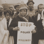 "A woman holding a protest sign reading ""Stop Police Killings"" from the 1960s"